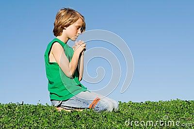 Christian child kneeling praying