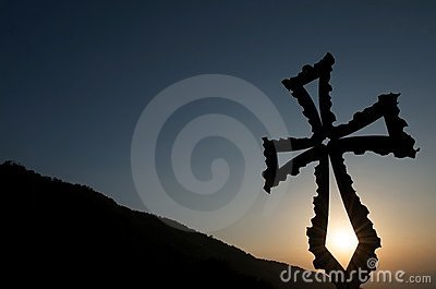 Christian cross at sunset with mountain backdrop Stock Photo