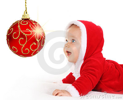 Christmas baby looking at a sparkling red ball