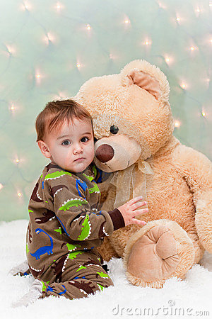 Christmas baby in pajamas hugging teddy bear