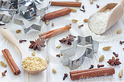 Christmas background with different spices, flour and cookie cutters on white wooden table Stock Photo