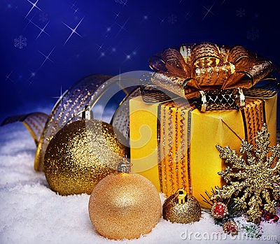 Christmas ball and gift box in snow.