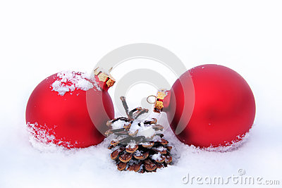 Christmas balls and pine cone in the snow