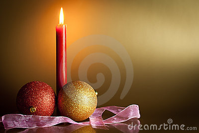 Christmas balls with red candle in background