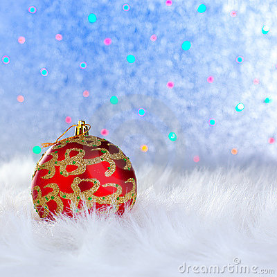 Christmas bauble on white fur and lights