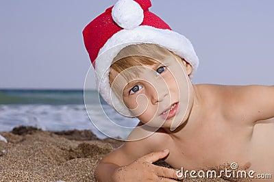 Christmas boy play on the beach