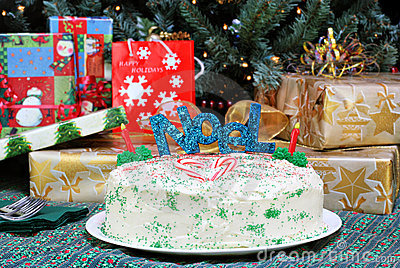 Christmas cake in front of tree and gifts.