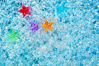 Christmas colorful glass stars on cold blue ice
