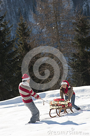 Christmas couple playing with gifts in the snow
