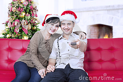 Christmas couple with santa s hats and holding remote control