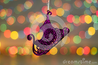 Christmas decorations. Close up photo of New Year purple sled. toy in colorful light Stock Photo