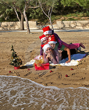 Christmas family laying on sand beach