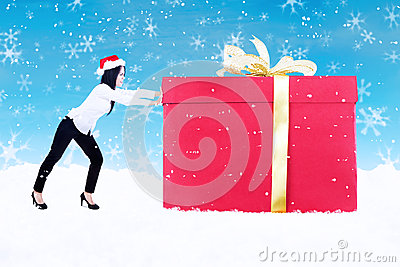 Christmas gift pushed by woman on blue background