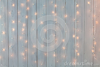 Christmas lights burning on a white wooden background. New Year back. Stock Photo