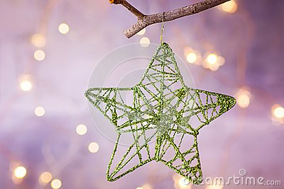 Christmas Ornament Glittering Woven Lace Star Hanging on Tree Branch. Sparkling Garland Lights Pastel Color Background. Stock Photo