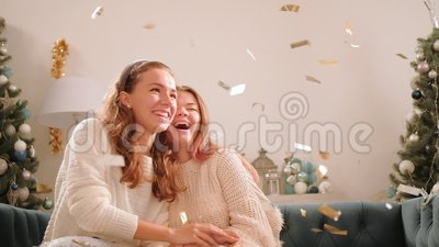 Christmas party family celebration joyful sisters. Christmas party. Family celebration. Joyful sisters having fun at home in shiny confetti rain stock video footage