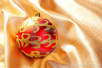 Christmas red bauble on golden  fabric