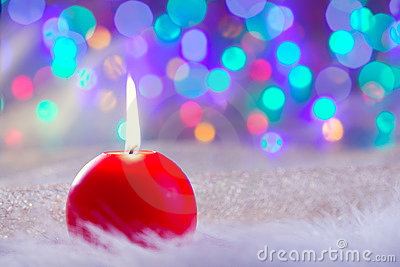 Christmas red candle on fur and colorful light