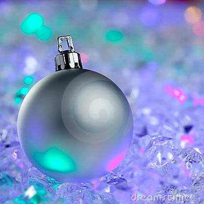 Christmas silver bauble on colorful glowing ice