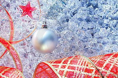 Christmas silver bauble and red ribbon on ice