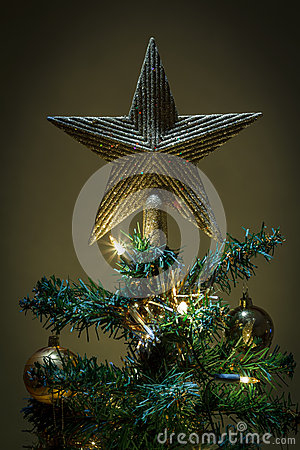 Christmas star on tree with yellow and green balls