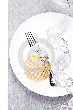Christmas table setting place with festive ornaments and silver