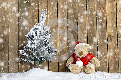 Christmas teddy bear sitting in the snow