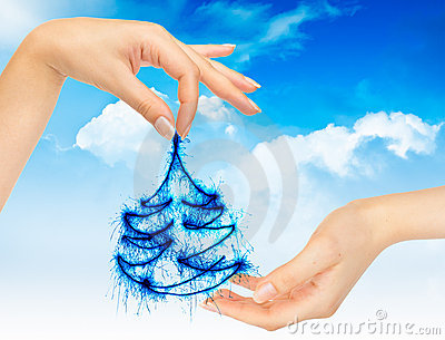 Christmas tree in hands on a blue sky
