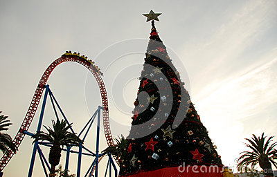 Christmas tree with a roller coaster in the background