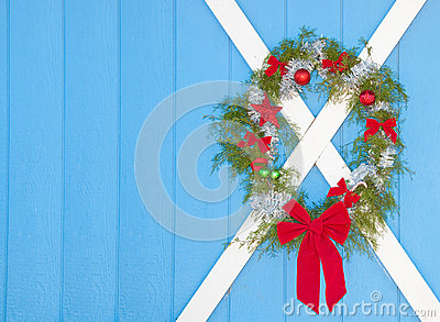 Christmas wreath hanging on a blue door