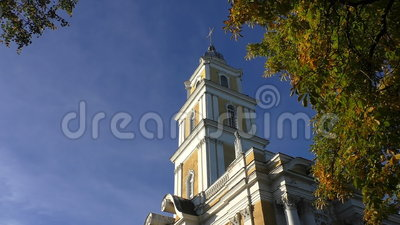 Church belfry and chestnut tree in autumn. Low angle shot of yellow white Christian church bell tower with cross on the top framed in foliage of green brown stock video