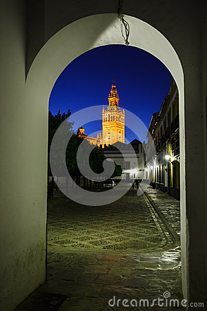 Church bell tower illuminated in arch to street