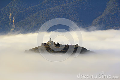 A church over a hill in the middle of a sea of ??fog