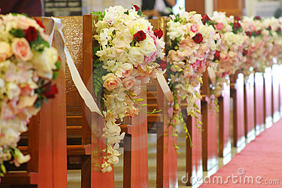 Church pews decorated with bouquets