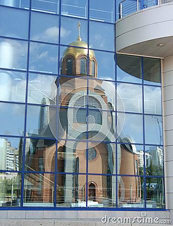 Church reflexion in windows of a modern building