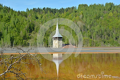 Church tower reflection in the lake of Geamana in the Apuseni Mountains, Romania