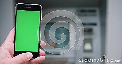 Ciérrese para arriba de la mano que sostiene un smartphone con la pantalla de visualización verde en la calle Llave de la croma v almacen de video