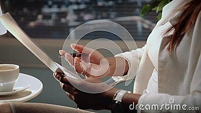 Ciérrese para arriba de las manos afroamericanas de la mujer de negocios que sostienen el contrato y la pluma metrajes