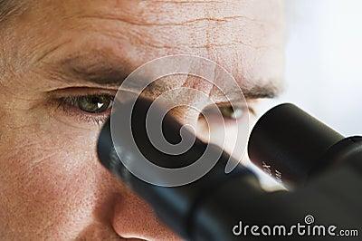 Ciérrese para arriba de los ojos del hombre que miran a través del microscopio