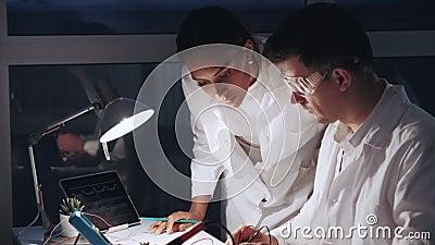 Ciérrese para arriba de mujer afroamericana y de hombre en el funcionamiento de vidrios protector en laboratorio de electrónica m almacen de metraje de vídeo