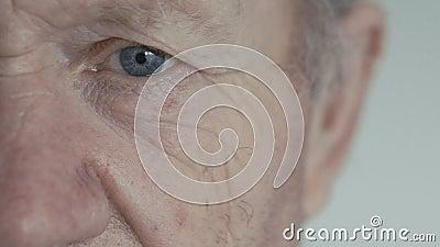 Ciérrese para arriba del ojo azul abierto del viejo hombre que mira la cámara en fondo almacen de video