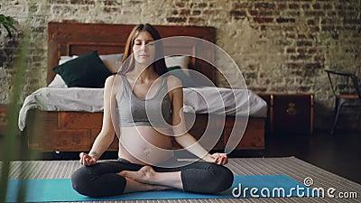 Ciężarna młoda kobieta jest siedząca w lotos pozie na joga macie z palmami na kolanach, oddychaniu i relaksować jej, Zdrowy zdjęcie wideo