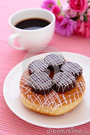 Ciambella del cioccolato zuccherato con una tazza di caffè