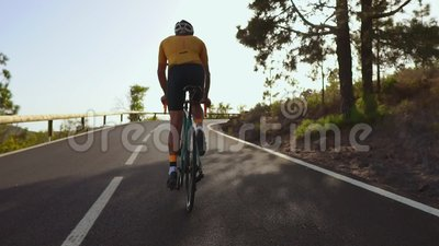 Ciclista che guida una bici su una strada aperta al tramonto archivi video