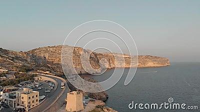 Cidade do turista com hotéis e estrada para o tráfego na costa rochosa do mar contra o céu, vista aérea video estoque