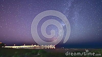 Cielo della Via Lattea sopra un pilastro di pesca sulla spiaggia in Florida Timelapse archivi video