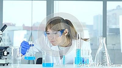 Científico de sexo femenino que mira la reacción que sucede en frasco en laboratorio