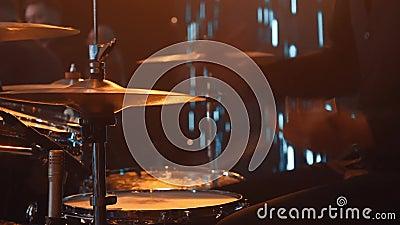Cierra las manos de un batería con un palo El grupo actúa en el escenario Un hombre toca los tambores en un grupo musical almacen de video