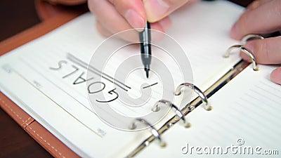 Cierre de la lista y objetivos de escritura a mano de un hombre de negocios en el diario metrajes