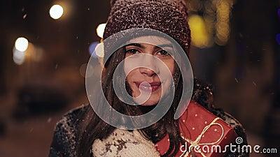 Cierre el retrato de la joven encantadora chica feliz en el sombrero de invierno y mitones, sosteniendo y abrazando la caja de re almacen de video